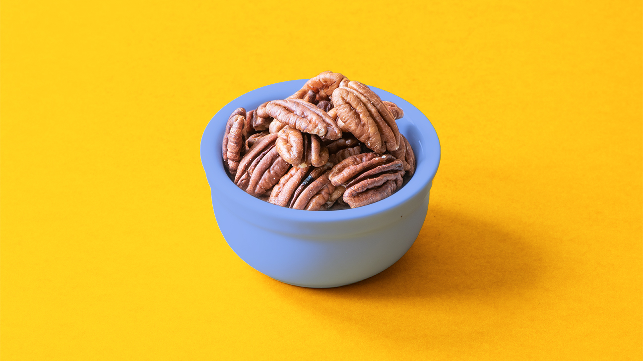 pecan nuts in a bowl on yellow background header